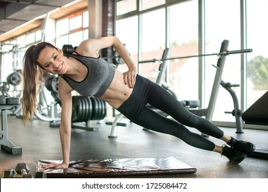 Attractive young woman doing side plank on fitness mat in the gym.