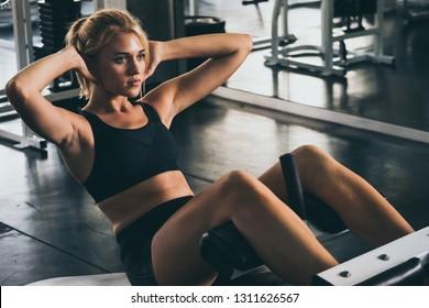 Attraktive junge Frau, die sich im Fitnessraum mit einer Maschine unterhält.