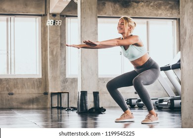 Attractive Young woman doing squat exercise at the gym.