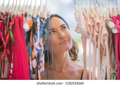Attractive young woman dreamily looks at things in the store - consumerism, sales, too much choice, temptation and dream big concepts
