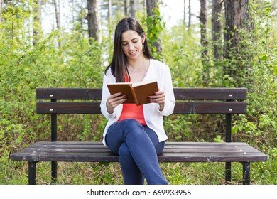 Attractive young woman dressed casually reads old book sitting on a wooden bench in the forest. Smiling while reading.