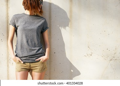attractive young woman dressed in a gray blank t-shirt posing against a background of a concrete wall in the rays of the setting sun