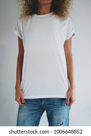 An attractive young woman dressed in a white blank t-shirt and blue jeans posing on a background of a white wall. Vertical mock up. empty space for you logo or design