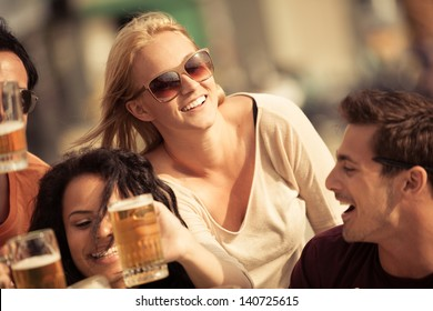 Attractive young woman drinking a beer on a beautiful sunny day