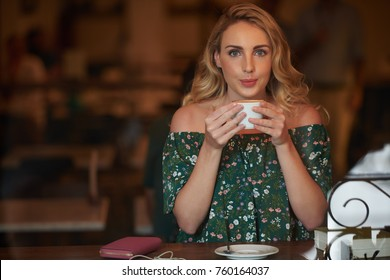 Attractive young woman drinking coffee in coffeshop