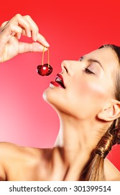Attractive young woman eating fresh cherry. Sexual lips, red lipstick. Healthy food concept. Cosmetics. Red background.