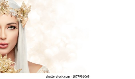 Attractive young woman in elf queen costume with golden christmas poinsettia flower wreath looking at camera while send a kiss. Beautiful young woman as christmas fairy