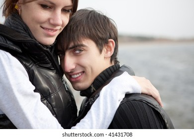 An attractive young woman embracing her handsome boyfriend