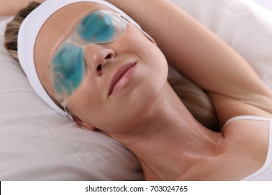 Attractive young woman with enjoying cooling eye gel mask. Beauty concept.