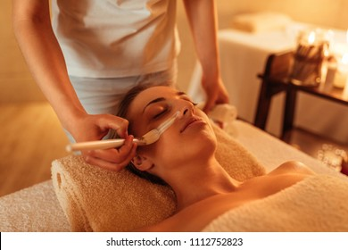 Attractive young woman enjoying a face treatment at a spa