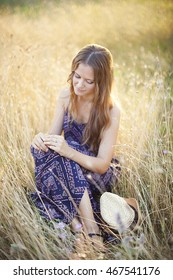 attractive young woman enjoying her time outdoors in summer sunset lights