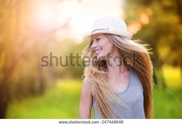Attractive young woman enjoying her time outside in park with sunset in background.