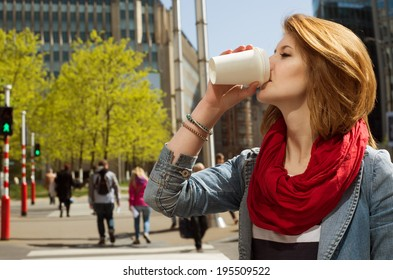 Attractive young woman enjoying a hot drink in a white paper cup against cityscape background