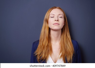 Attractive young woman enjoying a quiet moment standing meditating with her eyes closed and head tilted back, dark studio background with copy space