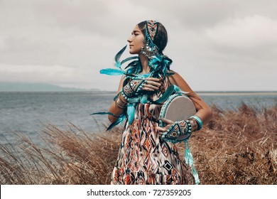 attractive young woman in ethnical costume on a field at sea