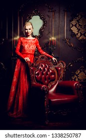 Attractive young woman in evening red dress posing in a luxury apartment. Classic vintage interior. Beauty, fashion. Evening makeup and hairstyle.