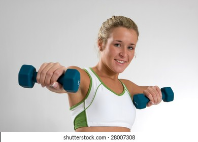 An attractive young woman exercises with dumbbells.