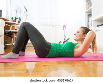 Attractive young woman is exercising in her living room. She is doing sit-ups while sitting on a exercising mat.