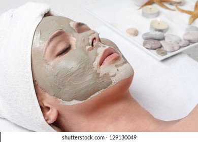 Attractive young woman with facial mask. Spa concept.
