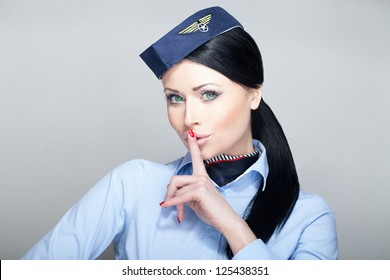 Attractive young woman flight attendant stewardess with green eyes quieting down