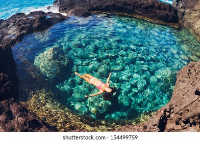 Attractive young woman floating in beautiful ethereal natural pool