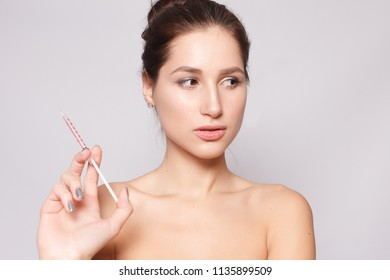 Attractive young woman gets cosmetic injection, isolated over white background. female hand holds a syringe for injection near face. Beauty Treatment.