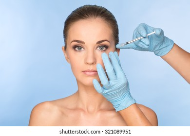Attractive young woman gets cosmetic injection. Doctors hands making an injection in face. Beauty Treatment.