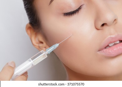 Attractive young woman gets cosmetic injection, isolated over white background. Doctors hands making an injection in face. Beauty Treatment.