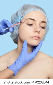 Attractive young woman gets cosmetic injection, an injection in the upper lip, over blue background. Doctors hands making an injection in face, close-up. Beauty Treatment. injection in the eyelid