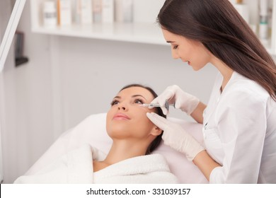 Attractive young woman is getting a collage injection in her face. She is sitting calmly at clinic. The expert beautician is filling female nasolabial wrinkles by hyaluronic acid and smiling