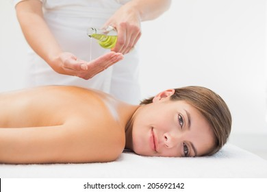Attractive young woman getting massage oil on her back at spa center