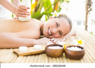 Attractive young woman getting massage on her back at spa center