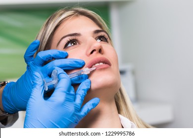 Attractive young woman is getting a rejuvenating facial injections. Medical procedure with hyaluronic acid.