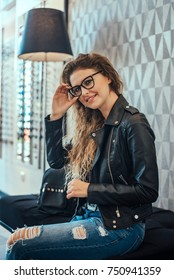 Attractive young woman with glasses inside optical store.