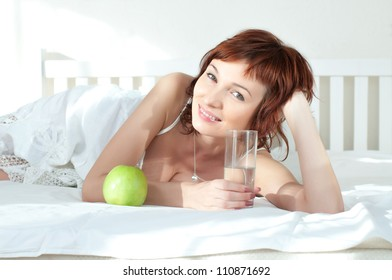 attractive young woman with an green apple and glass of water at bed