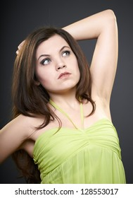 Attractive young woman in a green dress. Woman raised her hand. Looks to the upper-left corner. On a gray background