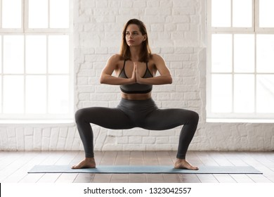 Attractive young woman in grey sportswear, leggings and bra practicing yoga at home or in yoga studio, beautiful girl standing in Sumo Squat, Goddess, working out, pilates exercise, close up