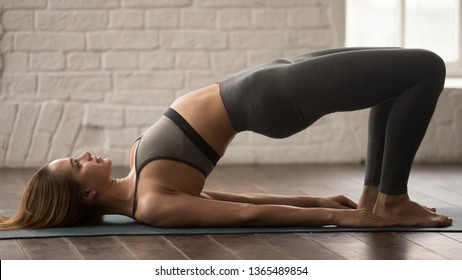 Attractive young woman in grey sportswear, leggings and bra practicing yoga, beautiful girl doing Glute Bridge exercise, dvi pada pithasana pose, working out at home or in yoga studio close up