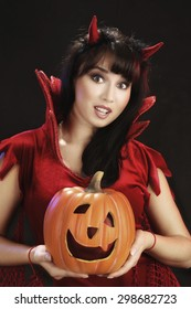 Attractive Young Woman in Halloween Costumes of Devils Holding a Pumpkin at the Black Background
