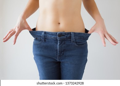 Attractive young woman hands stretching blue jeans and showing slim body after weight loss and healthy eating. Gray background. Front view.