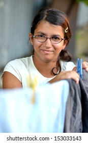 An attractive young woman hanging laundry.