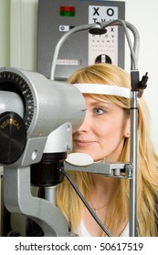 Attractive young woman having an eye sight examination at an optician's clinic