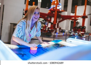 Attractive young woman is having fun in amusement park. Playing table hockey.