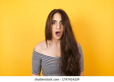 Attractive young woman having stunned and shocked look, with mouth open and jaw dropped, listening to friend's story in full disbelief, exclaiming: Wow, I can't believe this. Surprised girl. Shock