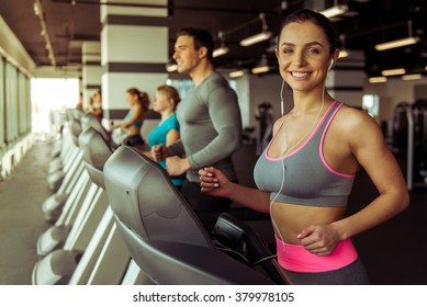 Attractive young woman in headphones running on a treadmill in gym, looking at camera and smiling