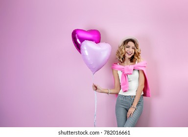 Attractive young woman with heart shaped air balloons on color background