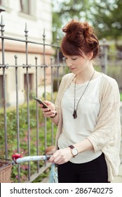 Attractive young woman with her hair in a bun standing holding her bicycle checking her mobile phone