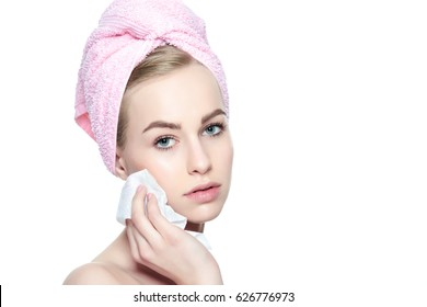 Attractive young woman with her hair wrapped in a towel, removing make up. Pretty girl with perfect complexion cleansing her face using soft face wipe . Isolated on white background with copy space.