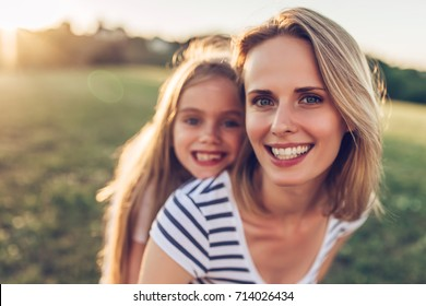 Attractive young woman with her little cute daughter are spending time together outdoors. Mom with daughter in park on a green grass during the sunset.