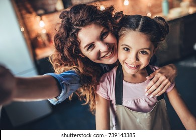 Attractive young woman and her little cute daughter are cooking on kitchen. Having fun together while making cakes and cookies. Smiling and making selfie.